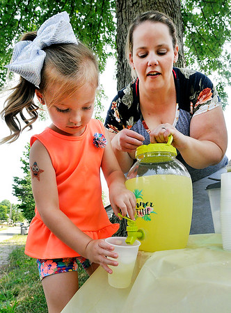 John P. Cleary   The Herald Bulletin<br /> Audrey Frye, 5, pours a cup of lemonade for a customer as her mother, Kayla Rebuck watches.