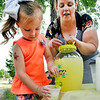 John P. Cleary | The Herald Bulletin<br /> Audrey Frye, 5, pours a cup of lemonade for a customer as her mother, Kayla Rebuck watches.