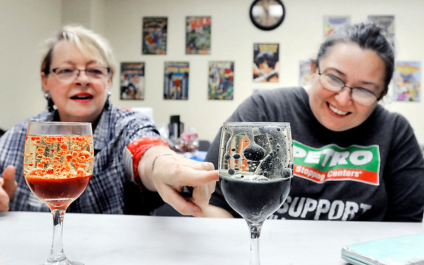 John P. Cleary | The Herald Bulletin <br /> Darlene Renner, and Iris Jensen react to the reaction of dropping an Alks Seltzer tablet into a glass of oil, water, and food coloring to create a 'Wine glass lave lamp' during the Alexandria Public Library's STEM night for adults this past week.