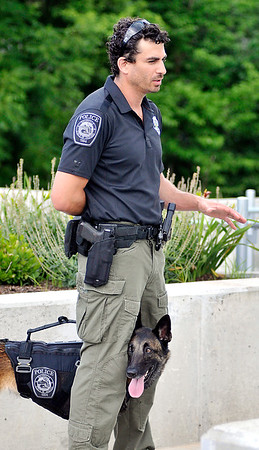 John P. Cleary | The Herald Bulletin <br /> Daleville Police officer Justin Melnick talks to people in Daleville Park as Dita, his <br /> K9 companion, stays close to him.