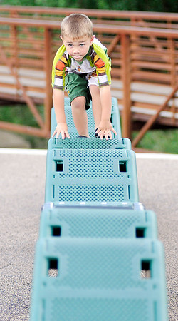 John P. Cleary   The Herald Bulletin <br /> Cooper Engelberth, 3, concentrates as he steadies himself while he moves along the reflex walk at the Daleville Park playground Tuesday afternoon.