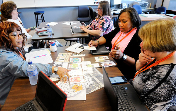 Don Knight | The Herald Bulletin<br /> Clockwise from left, Saundra Glover, Mae Wright and Paula Bolderson look through the clues from a breakout box during the eLead regional technology conference at Anderson High School on Tuesday.