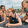 John P. Cleary | The Herald Bulletin<br /> Payton Pulley, 12, and Kailyn Flowers, 12, foreground, get a fresh application  of sunscreen from their friends, Morgan Baker, 13, and Harley Maynard, 12, as they enjoy the hot sun at the Alexandria pool Thursday afternoon.