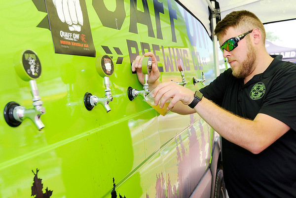 Don Knight | The Herald Bulletin<br /> Blake Butler pours a sample of Corn Crusher, a Pre-Prohibition Lager, at the Quaff On! Brewing Co. booth during Anderson On Tap downtown on Saturday.