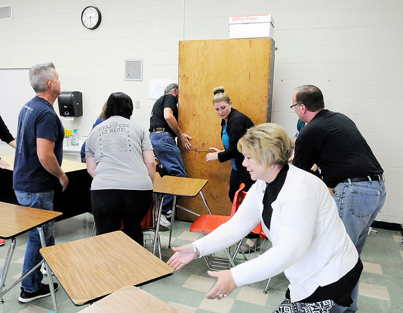 Don Knight | The Herald Bulletin<br /> Daleville teachers practice barricading a door during active shooter training involving local officers and teachers at Daleville High School on Saturday.