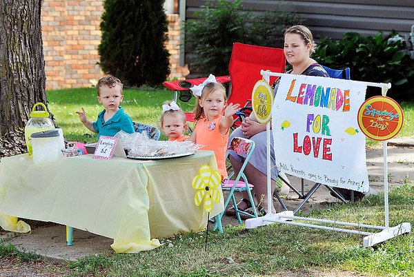 John P. Cleary | The Herald Bulletin<br /> As Kayla Rebuck watches, her children, Adrian Rebuck, 3, Alayna Rebuck, 1, and Audrey Frye, 5, wave a passing cars as they try to get customers for their Lemonade for Love stand at their house in Alexandria Thursday. The kids were running the lemonade stand to raise money for Beauty for Ashes.