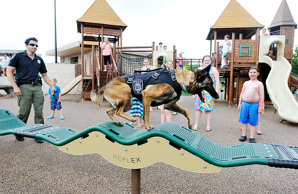 John P. Cleary   The Herald Bulletin <br /> Daleville Police officer Justin Melnick likes to take Dita, his K9 partner, to the Daleville Park where Dita loves to run and jump on the playground equipment, much to the delight of the kids that are there.