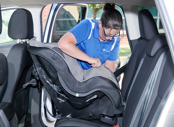 Don Knight | The Herald Bulletin<br /> Dannica Minnick installs a car seat during the annual Community Safety Fair organized by the Children's Bureau at Anderson High School on Wednesday. Staff from both St. Vincent and Community were on hand to help parents install new seats that were being handed out during the event.