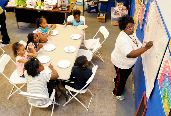 Don Knight   The Herald Bulletin<br /> Corrine Rolling teaches kindergarten and first grade students how to read a clock during Summer Camp at the Anderson Township Trustee Youth Center.