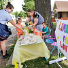 John P. Cleary | The Herald Bulletin<br /> Mail carrier Angie Rose puts down her money as Kayla Rebuck helps her daughter, Audrey Frye, 5, pour a cup of lemonade.