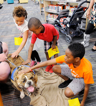 Don Knight | The Herald Bulletin<br /> From left, Essence Rochell, Jeremiah Webb and Aidan Cottrell pet Tim Greenlee's Old English Bulldog Norman from Love on a Leash as Anderson Public Library kicked off their Summer Reading Program with a carnival on Thursday. The program's goal for the summer is 1,000,000 minutes.