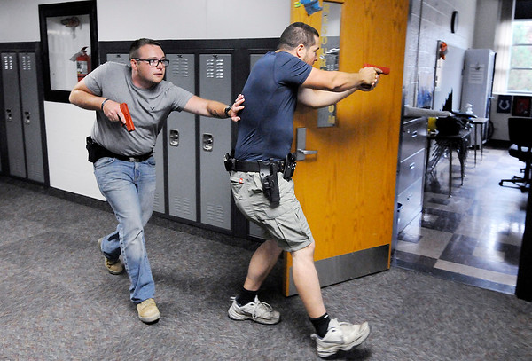 Don Knight | The Herald Bulletin<br /> From left, Justin Royse and Dakota Steele practice moving down a halway during active shooter training involving local officers and teachers at Daleville High School on Saturday.
