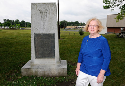 Don Knight | The Herald Bulletin Cecilia Calvert stands next to the monument to graduates of Anderson High School who died in World War I that is located next to the Wigwam. Calvert is leading an effort to have the memorial cleaned and moved to Maplewood Cemetery.