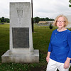 Don Knight | The Herald Bulletin<br /> Cecilia Calvert stands next to the monument to graduates of Anderson High School who died in World War I that is located next to the Wigwam. Calvert is leading an effort to have the memorial cleaned and moved to Maplewood Cemetery.