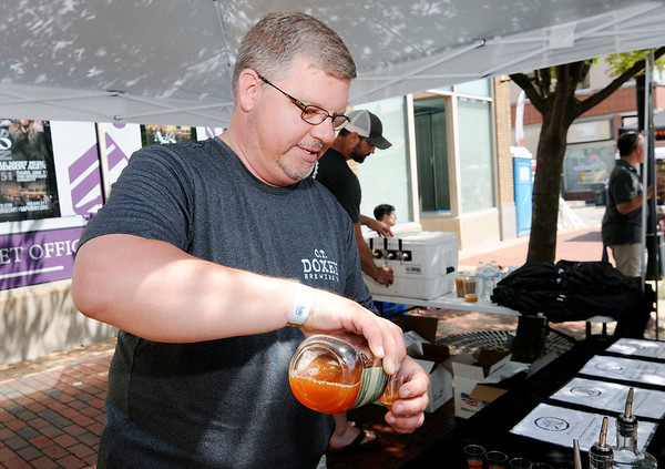 Don Knight | The Herald Bulletin<br /> Jason Oakley pours a sample of Apple Pie Moonshine at Oakley Brothers C.T. Doxey booth during Anderson On Tap downtown on Saturday.