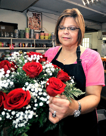 John P. Cleary | The Herald Bulletin <br /> Shari Collins, manager of the Posy Shop, works on an arrangement of roses Monday afternoon. The family run business will close it's doors the first of August after 70 years.