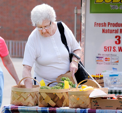 Don Knight | The Herald Bulletin<br /> Barbara Dulworth picks out some produce from the Dublin Farm booth at the Anderson City Market on Saturday.