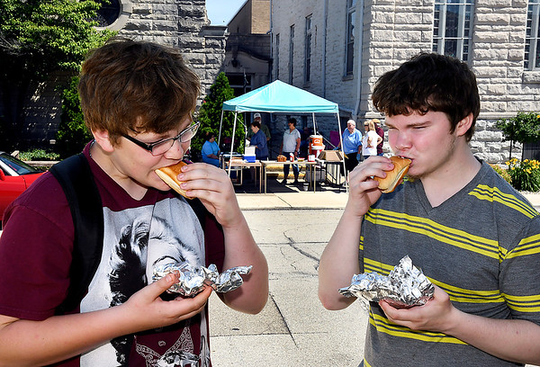 John P. Cleary | The Herald Bulletin Nick Harsh, 13, and Caleb Ground, 20, enjoy their hot dogs from the Central Christian Church's free hot dog lunch Friday afternoon. The church hosts the free lunch each Friday during the summer from 11 a.m. to 1 p.m.