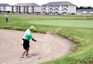 John P. Cleary | The Herald Bulletin   These golfers play the 17th hole at Elwood Golf Links as several of the Bison Ridge Estates apartment buildings overlook the 17th fairway.