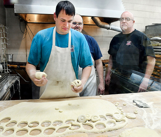 John P. Cleary | The Herald Bulletin <br /> Daniel Phillips cuts the rings for doughnuts as fellow bakers, Russell Halverson,  and Mike Allison look on at Deluxe Donuts. The trio have a combined 72 years of doughnut-making experience.