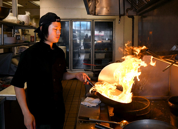 John P. Cleary | The Herald Bulletin<br /> Chef Xing Zhou works in the kitchen of his restaurant, the Lantern House Asian Bistro, on South Scatterfield Road.