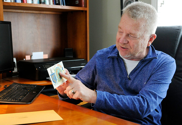 Don Knight | The Herald Bulletin<br /> Mike Fox holds a post card sent home by his father George Fox who served during D Day and the Battle of the Bulge.