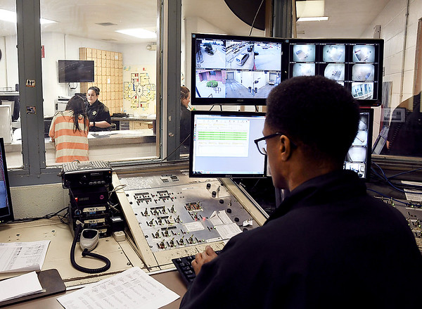 John P. Cleary | The Herald Bulletin <br /> Madison County jail officer Ollie Dixon, right, works in the control room as jail officer Taylor Fleming, backgound, works with a inmate at the book-in desk.
