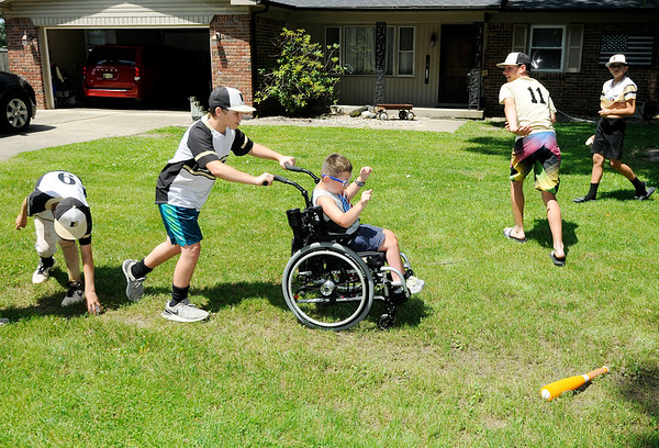 Don Knight | The Herald Bulletin<br /> Garrett Imel plays Wiffle Ball with members of a travel team from Lapel as they stopped by his  lemonade stand on Saturday.