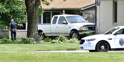 John P. Cleary | The Herald Bulletin   Anderson Police Department officer checks the scene after this stolen pickup truck crashed into a house at Graceland Ave. and University Blvd. Saturday morning after a low-speed chase. The driver, Phillip Tolley, 30, of Zionsville, fled the scene after crashing and then fired multiple shots at pursuing officers before being taken into custody.