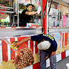 John P. Cleary | The Herald Bulletin<br /> Gareth Forsberg, inside, cleans the windows as Ruby Gonzalez cleans the outside of the Yum Yum Shoppe food stand Monday afternoon at Falls Park in Pendleton. They were setting up for the annual Pendleton June Jamboree that runs June 4-8.