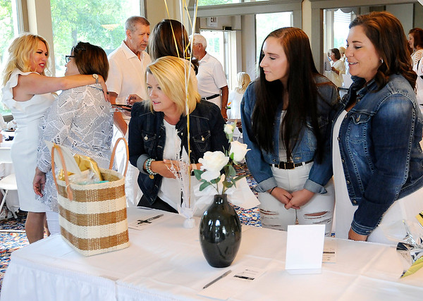 Don Knight | The Herald Bulletin<br /> From left, Alison Boerner, Sydney Carey and Amy Carey look at silent auction items as St. Vincent Anderson celebrated their 125th Birthday with a White Party at the Anderson Country Club on Thursday.