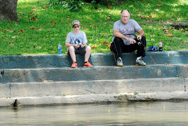 Don Knight | The Herald Bulletin<br /> Kyson Fields, 9, fishes with his grandfather Fred Welborn at Falls Park in Pendleton on Wednesday.