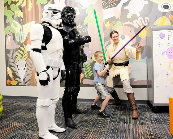 "Don Knight | The Herald Bulletin<br /> Mikey Porter, 7, poses with members of the 501st Legion during Anderson Public Library's summer reading program kickoff on Thursday. The program, ""A Universe of Stories,"" begins on Saturday. You can find more information and register online at the library's website."