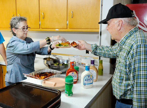 Don Knight | The Herald Bulletin<br /> Julia Christenson hands Jim Hensley a dinner of stuffed shells and salad during the weekly dinner and dance at the Rangeline Community Center on Thursday. The Center is trying to raise enough money to replace the heating and air conditioning system.
