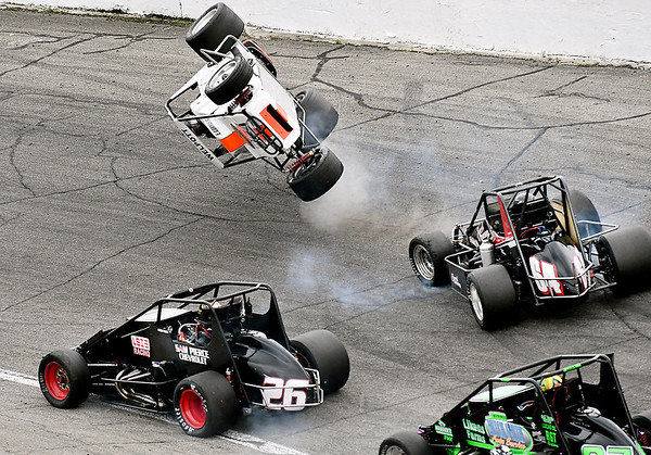 John P. Cleary | The Herald Bulletin<br /> Travis Welpott, of Pendleton, flips in turn two after making contact with the #64 car of Justin Grant on lap 47, as eventual winner, #26, Aaron Pierce gets by on the inside. Welpott let the first 46 laps before crashing.