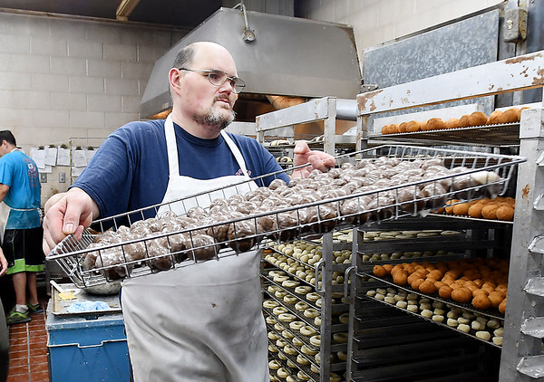 John P. Cleary | The Herald Bulletin <br /> Russell Halverson puts up a rack of freshly grazed doughnut holes at Deluxe Donuts. Halverson has worked at Deluxe for 25 years.