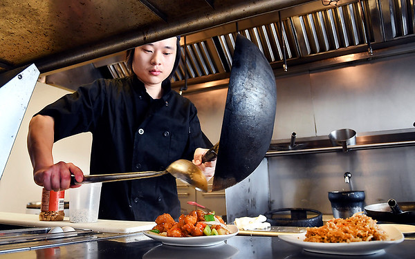 John P. Cleary | The Herald Bulletin<br /> Chef Xing Zhou plates up a dish at his restaurant, the Lantern House Asian Bistro, on South Scatterfield Road.