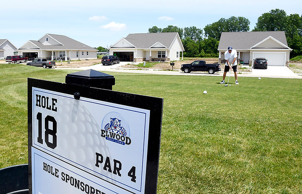 John P. Cleary | The Herald Bulletin   Steve Hobbs prepares to tee off on the 18th hole of Elwood Golf Links as some of the single family homes of the Bison Ridge Estates housing development line the street in the background.