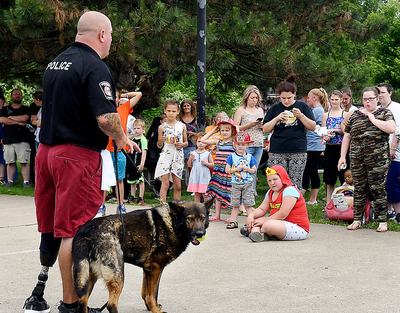 John P. Cleary | The Herald Bulletin<br /> Anderson Police officer Marty Dullworth gives a demonstration with his K-9 companion, Rico, during the department's first block party Saturday at Walnut Street Park. Saturday's event was the first of nine block party's scheduled throughout the city this summer.