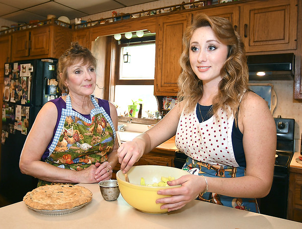 John P. Cleary | The Herald Bulletin<br /> Rebekah Noble, right, works on an apple pie filling as her mother, Mary Ann Noble, looks on. Rebekah has a long family history of baking.