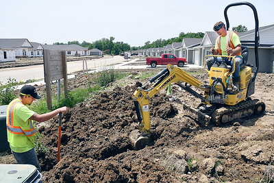 John P. Cleary | The Herald Bulletin   Jaron Burry and Adam Orr, from QC Communications, work at Bison Ridge Estates putting in cable for the development project Friday. Bison Ridge Estates is a $25 million housing project built around Elwood Golf Links in Elwood.