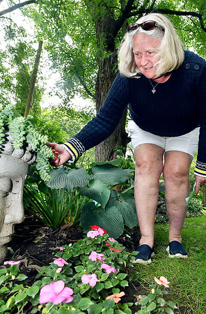 John P. Cleary | The Herald Bulletin   Michelle Sizelove checks out the different plants and flowers in Kay and Don Bale's backyard garden as part of this year's annual Madison County Master Gardener Association garden tour held Saturday.