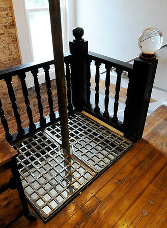 Don Knight | The Herald Bulletin<br /> Tim Perry kept the fire pole and added a grate to cover the hole in the floor but still allow a view to the space below in the former fire station on third street.