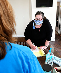 Molly Cooper, of Cooper Insurance in Lapel, writes a receipt for a client while wearing her mask and having hand sanitizer and face masks on the desk for her clients as well.