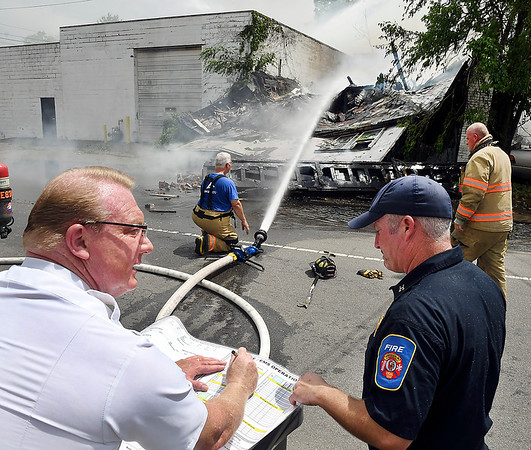 Anderson Fire Department Fire Chief Dave Cravens, left, assists at the scene of a structure fire in the 1600 block of Brown Street Wednesday afternoon.