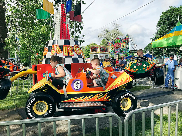 Hundreds of residents took advantage of the break from the rainshowers Tuesday for opening day of the Pendleton Lions Club's June Jamboree. Youngsters, such as Charlotte Pickrell, 6, and her brother Dean Pickrell, 5, seen here driving on the Jump Around, braved the rides, won prizes at the games and enjoyed corn dogs, cotton candy and lemonade. The June Jamboree, the first in two years because of the COVID-19 pandemic, continues through Saturday.