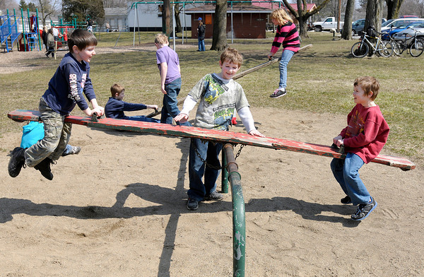 From left, Logan Upchurch, Tony Upchurch and Andrew Killian play on the seesaw at Falls Park in Pendleton on Friday. After a cold snowy start to the week clear skies and a high in the 50s made Friday a great day to get outside.