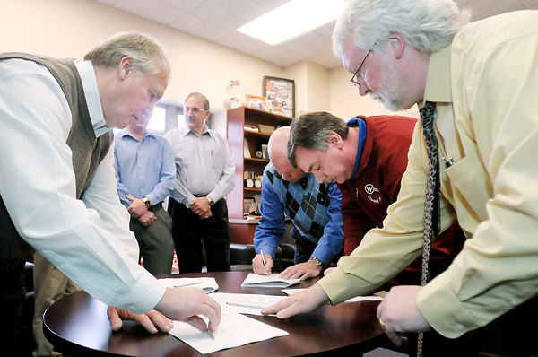 From left, President of Warner Bodies Richard Manasek, Elwood Redevelopment Commission President Tom Austin, Mayor Ron Arnold and Economic Development Director Bill Savage sign paperwork after announcing Warner Bodies plans to move their production from Noblesville to the former Plastech facility in Elwood. The move will create 150 new jobs in Elwood.