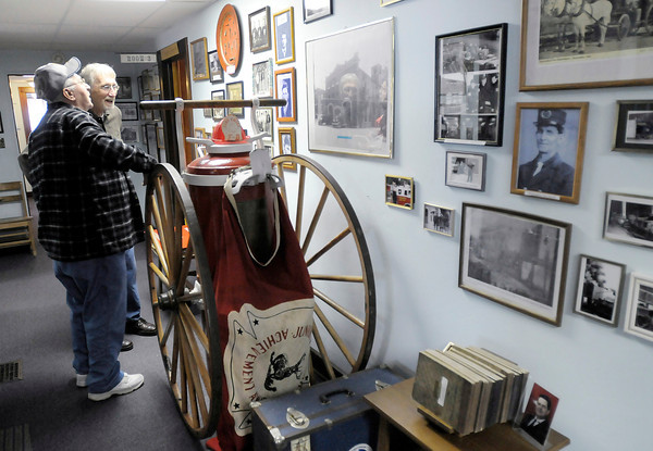 Alexandria Monroe Historical Society Vice President Mike Lynch, right, and Jim Flecker look at old photos in the halls of the Alexandria Historical Museum on Saturday. The museum opened for the first time this year on Saturday.