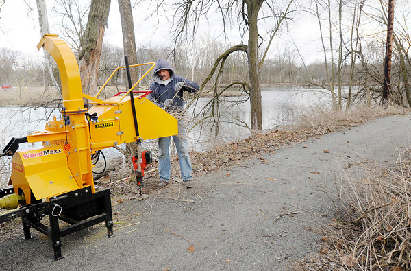 """Mike Truman chips brush he cleared along the trail around the lake at Shadyside on Wednesday. A member of Madison Park Church of God Truman first volunteered in the city parks as part of the church's """"Do Something"""" campaign three years ago. Truman has now made volunteering in the city parks a year round ministry. """"It's a good way to be a witness to other people and the city,"""" Truman said."""